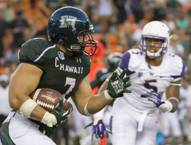 Hawaii running back Joey Iosefa (7) looks for an opening as Washington defensive lineman Joe Mathis (5) watches the third quarter of an NCAA college football game, Saturday, Aug. 30, 2014, in Honolulu. (