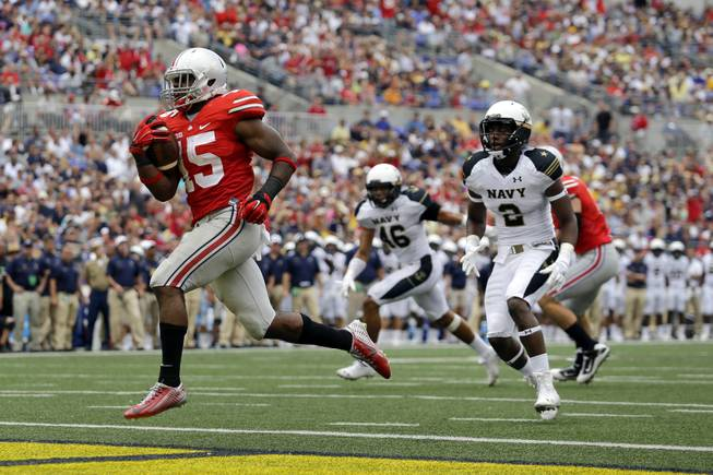 In this Aug. 30, 2014, file photo, Ohio State running back Ezekiel Elliott, left, runs past Navy safety Parrish Gaines (2) and linebacker Chris Johnson (46) for a touchdown in the second half of an NCAA college football game in Baltimore. After a 34-17 victory over Navy in the opener, coach Urban Meyer is pleased with the job done by Elliott, who gained 44 yards on 12 carries including this 10-yard touchdown run.