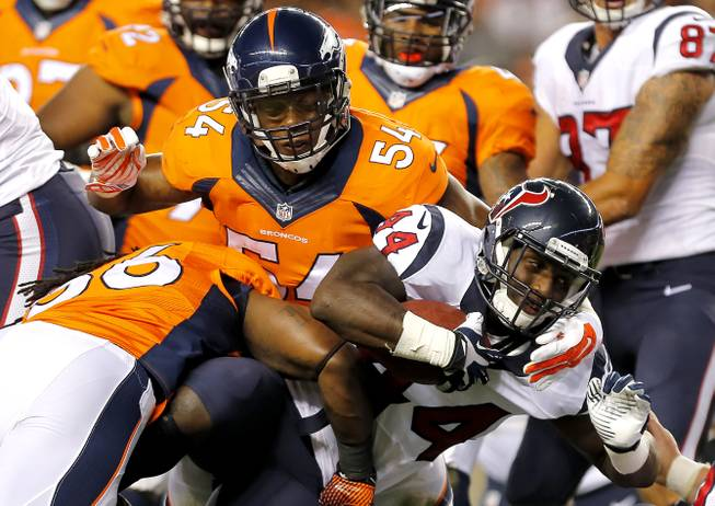 Houston Texans running back Alfred Blue (44) is tackled by Denver Broncos outside linebacker Nate Irving (56) and Brandon Marshall (54) during the first half of an NFL preseason football game, Saturday, Aug. 23, 2014, in Denver.