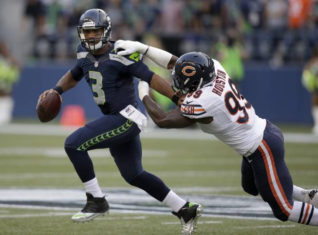 Seattle Seahawks quarterback Russell Wilson (3) tries to escape the grasp of Chicago Bears defensive end Lamarr Houston in the first half of a preseason NFL football game, Friday, Aug. 22, 2014, in Seattle. The Seahawks won 34-6.