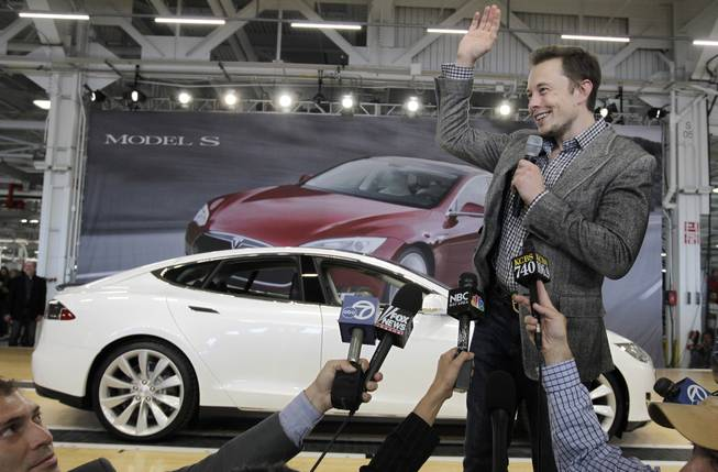In this June 22, 2012 file photo, Tesla CEO Elon Musk waves during a rally at the Tesla factory in Fremont, Calif. Tesla Motors has selected Nevada for a massive, $5 billion factory that it will build to pump out batteries for a new generation of electric cars, a person familiar with the company's plans said Wednesday, Sept. 3, 2014.