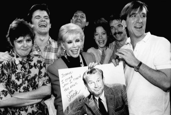 "Comedian Joan Rivers, center, holds up a poster of Jack Paar, former host of NBC's ""Tonight Show,"" which was given to her by the cast of National Lampoon's ""Class of ?86"" in New York, June 5, 1986. Rivers will host her own late night talk show this fall, competing with the ""Tonight Show"" and current host Johnny Carson. With Rivers are from left: Annie Golden, Rodger Bumpus, Tommy Koenig, Veanne Cox, John Michaels Higgins, and Brian Brucker O?Connor."