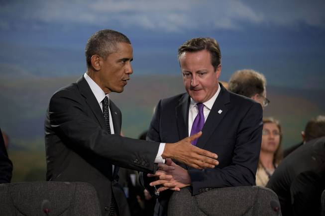 U.S. President Barack Obama and British Prime Minister David Cameron, right, speak before taking their seats at the start of a NATO-Afghanistan round table meeting during a NATO summit at the Celtic Manor Resort in Newport, Wales on Thursday, Sept. 4, 2014. In a two-day summit leaders will discuss, among other issues, the situation in Ukraine and Afghanistan.