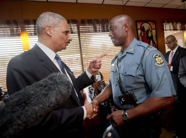FILE - In this Aug. 20, 2014 file photo, Attorney General Eric Holder talks with Capt. Ron Johnson of the Missouri State Highway Patrol at Drake's Place Restaurant in Florrissant, Mo. The Justice Department plans to open a wide-ranging investigation into the practices of the Ferguson, Missouri, Police Department following the shooting last month of an unarmed black 18-year-old by a white police officer in the St. Louis suburb, a person briefed on the matter said Wednesday, Sept. 3, 2014.