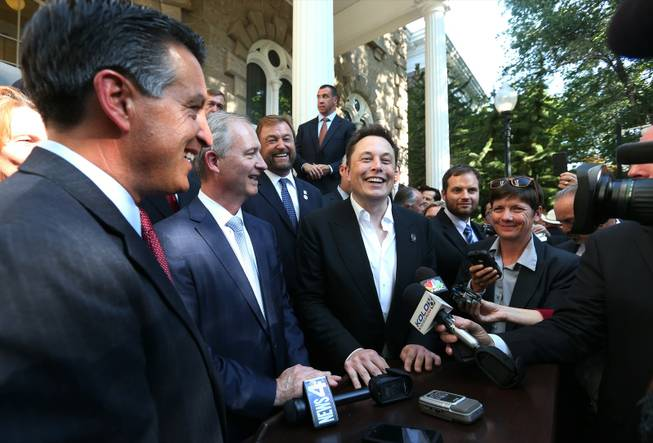 From left, Nevada Gov. Brian Sandoval; Steve Hill, executive director of the Governor's Office of Economic Development; and Telsa Motors CEO Elon Musk answer questions after a news conference at the Capitol in Carson City on Thursday, Sept. 4, 2014.