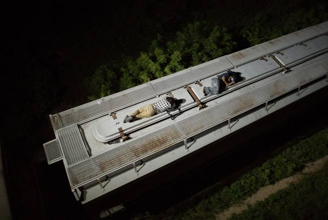 AP10ThingsToSee- In this Aug. 26, 2014 photo, Central American migrants sleep atop a moving freight train as it heads north from Arriaga toward Chahuites, Mexico.