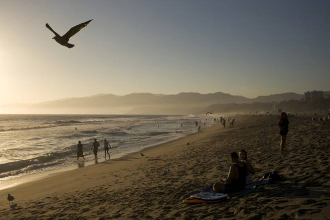 AP10ThingsToSee- People walk along the beach Friday, Aug. 29, 2014, in Santa Monica, Calif. The highest number of Californians since the recession were expected to travel over the Labor Day holiday weekend.