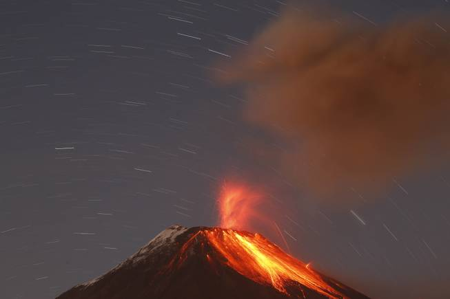 AP10ThingsToSee- The Tungurahua volcano throws ash and stones during an eruption seen from Banos, Ecuador, Sunday, Aug. 31, 2014. The volcano entered an eruptive phase in 1999 and continues to this day.