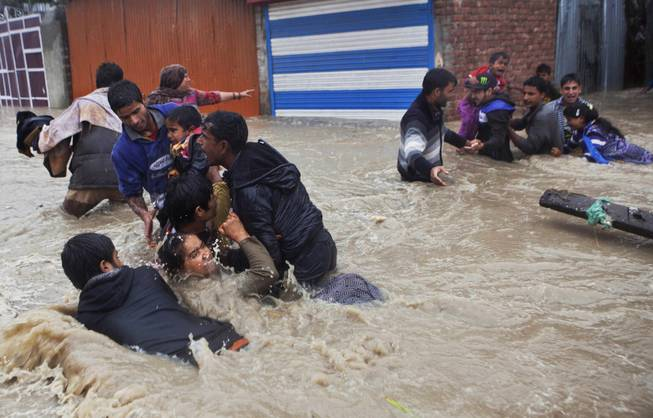 AP10ThingsToSee- Kashmiri residents wade through floodwaters in Srinagar, India, Thursday, Sept. 4, 2014. At least 100 villages across the Kashmir valley were flooded by overflowing lakes and rivers.
