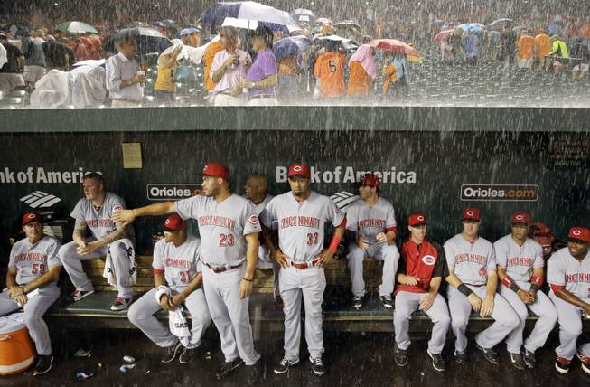 AP10ThingsToSee- Members of the Cincinnati Reds watch from the dugout as heavy rain falls during a rain delay in the first inning of an interleague baseball game against the Baltimore Orioles, Tuesday, Sept. 2, 2014, in Baltimore.