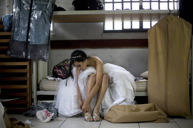 "AP10ThingsToSee- A teenage girl from the Santa Marta ""favela"" slum puts on a pair of high heels for a group debutante ball organized by the Pacifying Police Unit from her neighborhood in Rio de Janeiro, Brazil, Friday, Aug. 29, 2014."
