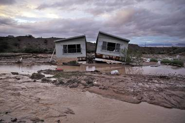 Receding floodwater surrounds a home in Moapa, Monday, Sept. 8, 2014. Flooding throughout the area damaged homes and roads.