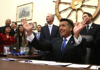 Surrounded by lawmakers and staff members at the Capitol in Carson City on Thursday, Sept. 11, 2014, Nevada Gov. Brian Sandoval signs into law an unprecedented package of incentives to bring Tesla Motors' $5 billion battery factory to the state.