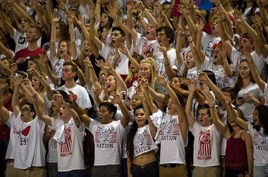 A very vocal section of visiting Coronado Cougar fans cheers on their team against the Patriots at Liberty High School on Friday night.