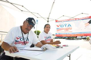 Miguel Amaral and Stephanie DeJesus attempt to register voters outside the E. Saraha DMV, Friday Sept. 12, 2014. Amaral and DeJesus are field registrars for Mi Familia Vota, a non-partisan organization that encourages civic engagement among the Hispanic community.