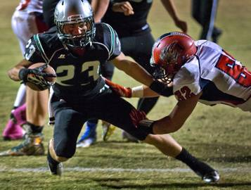 Green Valley's Albert Lake #3 turns the corner on a run while trying to break a tackle by Coronado's Aaron Cotton #52 on Friday, October 10, 2014.