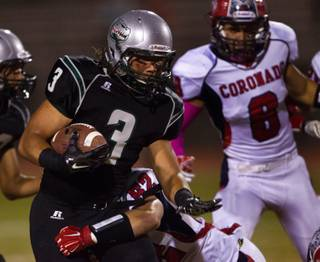 Green Valley's .Brenan Adams #3 turns the corner on a run while trying to break a tackle by Coronado's Aaron Cotton #52 on Friday, October 10, 2014.