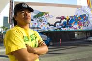 Artist Sush Machida poses by a mural he is creating with fellow artist Tim Bavington on the side of the Emergency Arts building at Fremont and Sixth streets in downtown Las Vegas Sunday, Oct. 12, 2014.