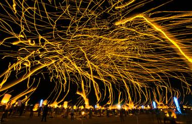 Lanterns float into the night sky on a long exposure leaving light trails as more are inflated for release during the Rise Lantern Festival at Jean Dry Lake Bed on Saturday, Oct. 18, 2014, in Jean.