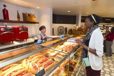 Emily Moheganrooney helps Caesars Entertainment PR intern Sha'Mell Henry with a sandwich order at Fulton Street Food Hall on Wednesday, Oct. 22, 2014, at Harrah's.