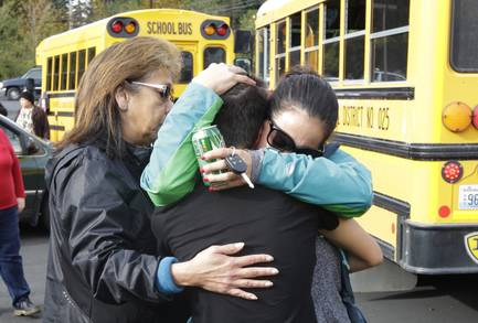 People embrace in front of school buses at a church Friday, Oct. 24, 2014, where students were taken to be reunited with parents following a shooting at Marysville Pilchuck High School in Marysville, Wash.