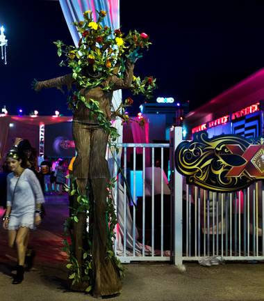 A large human-costumed tree greets attendees at the entrance of the Dos Equis Masquerade during day 2 of the Life is Beautiful Festival on Friday, October 24, 2014.