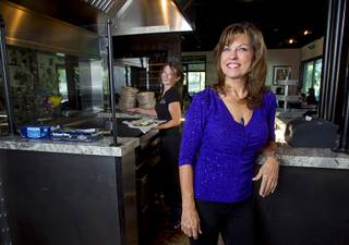 Owner Lola Pokorny poses by the oyster grill at Lola's Louisiana Kitchen, 1220 N. Town Center Drive, in Summerlin Wednesday, Oct. 29, 2014. Server Kelly Eshleman is at left. The restaurant, the second Lola's location, celebrated it's grand opening on Oct. 21.
