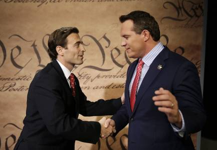 Adam Laxalt, left, shakes hands with Nevada Secretary of State Ross Miller before they debate Friday, Oct. 10, 2014, in Las Vegas. Laxalt and Miller are facing each other in a race for attorney general in Nevada. (AP Photo/John Locher)​