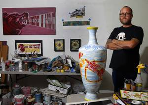 JW Caldwell poses by a ceramic vessel by artist Miguel Rodriguez  that will be part of Hammer & Cycle's third annual Bikes For Brats charity art auction.