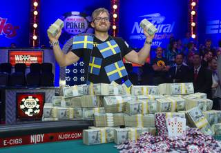 Martin Jacobson, 27, of Sweden stands with cash after beating Felix Stephensen of Norway to win the $10 million first-place prize during the 2014 World Series of Poker Main Event Final Table on Tuesday, Nov. 11, 2014, at the Rio.