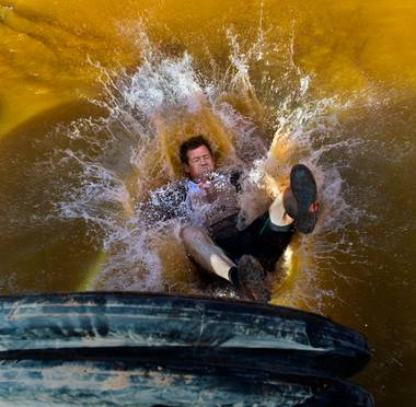 "A participant splashes into the water while making his way through the ""Sewage Outlet"" obstacle during the World's Toughest Mudder about Lake Las Vegas on Saturday, November 15, 2014."
