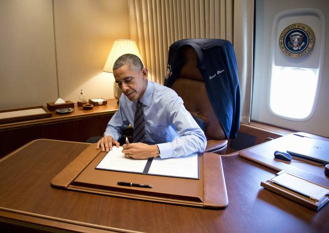 President Barack Obama signs two presidential memoranda associated with his actions on immigration in his office, on Air Force One as he arrives at McCarran International Airport in Las Vegas, Friday, Nov. 21, 2014.