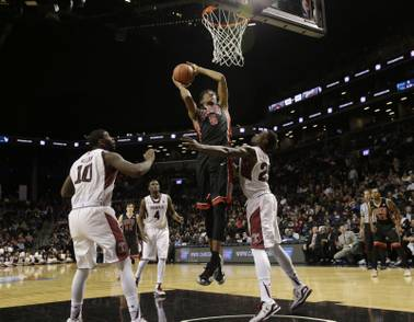 UNLV's Christian Wood, center, drives to the basket past Temple defenders during the second half of a game for third place in the Coaches vs. Cancer Classic on Saturday, Nov. 22, 2014, in New York. UNLV defeated Temple 57-50.