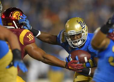 UCLA's Myles Jack, right, stiff-arms Southern California linebacker Hayes Pullard as he runs the ball Saturday, Nov. 22, 2014, in Pasadena, Calif.