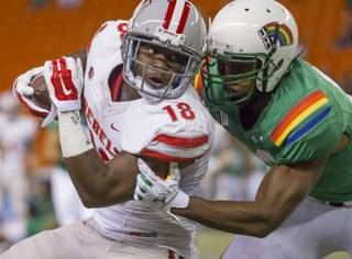 UNLV wide receiver Marcus Sullivan (18) is tackled by Hawaii defensive back Trayvon Henderson (39) after Sullivan caught a pass in the first quarter of an NCAA college football game, Saturday, Nov. 22, 2014, in Honolulu.
