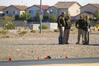 Metro Police officers confer near the area where a man and a baby were hit by a car on South Rainbow Boulevard near Warm Springs Road Monday, Nov. 24, 2014.