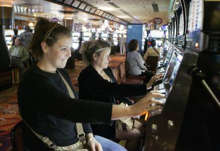 In this Aug. 30, 2009, file photo, Caitlin and Lynne Byers play the slot machines at Foxwoods Resort and Casino in Mashantucket, Conn. Foxwoods, North America's largest casino resort, is reducing the number of slot machines and table games to free up space for nightclubs and other new attractions as it adapts to fierce competition from neighboring states, the new CEO said in an interview Monday, Nov. 24, 2014, with The Associated Press.