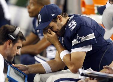 Dallas Cowboys quarterback Tony Romo puts his hand to his face as he sits on the bench late during the second half against the Philadelphia Eagles on Thursday, Nov. 27, 2014, in Arlington, Texas.
