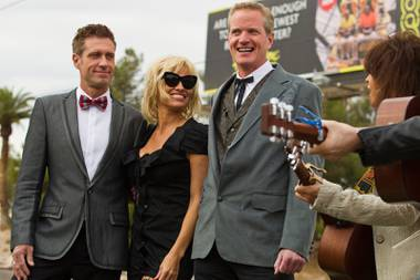 "Jack Ryan, Pamela Anderson and Dan Mathews listen to a song by Chrissie Hynde during their wedding ceremony at the ""Welcome to Fabulous Las Vegas"" Sign on Thursday, November 27, 2014. Mathews of People for the Ethical Treatment of Animals marries his longtime partner Jack Ryan there before a small wedding party."