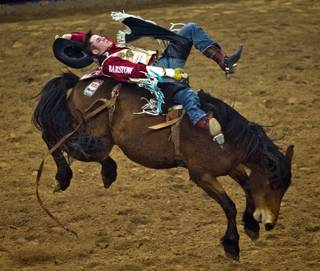 Bareback rider Austin Foss from Terrebonne, Ore., catches some air even before leaving the chute during the 56th Wrangler  National Finals Rodeo at the Thomas & Mack Center on Tuesday, December 9, 2014. L.E. Baskow.