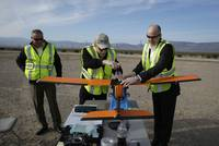 From left, Joe Burns, Scott Carrigan and Dan Johnson of Sensurion Aerospace prepare the Sensurion Aerospace Magpie commercial drone for a flight Friday, Dec. 19, 2014, near Boulder City.