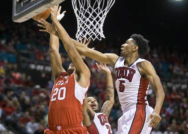 UNLV forward Christian Wood, right, deflects a shot under the basket from Utah forward Chris Reyes at the MGM Grand Garden Arena on Saturday, Dec. 20, 2014.