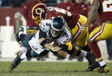 Philadelphia Eagles quarterback Mark Sanchez is stopped on a short carry by Washington Redskins linebacker Trevardo Williams during the second half of an NFL football game in Landover, Md., Saturday, Dec. 20, 2014.