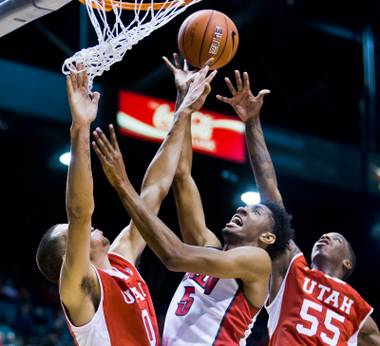 UNLV guard Rashad Vaughn (1) tips a ball at the basket between Utah forward Brekkott Chapman (0) and Utah forward Delon Wright (55) during their men's basketball game at the MGM Garden Arena on Saturday, December 20, 2014.