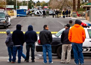Onlookers watch as crime scene investigators work the scene of a LVMPD helicopter down in the street at 23rd Street north of Bonanza Road after a crash landing on Wednesday, December 31, 2014.