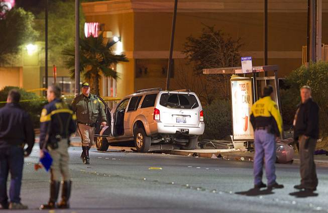 Metro Police and crime scene analysts investigate an accident Saturday, Jan. 10, 2015, after an SUV crashed into a bus stop, striking a woman and two children on Rainbow Boulevard north of Lake Mead Boulevard.