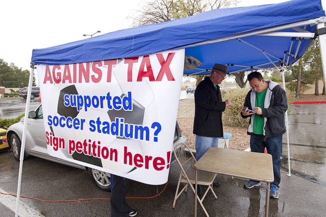 Las Vegas City Councilman Bob Beers, left, looks on as Ari Stotland signs a petition opposing spending taxpayer money on a downtown soccer stadium Sunday, Jan 11, 2015. Opponents need 2,306 signatures to bring the project up for a referendum.