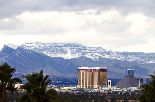 Snow-covered mountains are shown behind the Mandalay Bay and Luxor casinos Monday, Feb. 23, 2015. The Las Vegas Ski and Snowboard Resort on Mount Charleston received 10 inches of new snow, according to the weather service.
