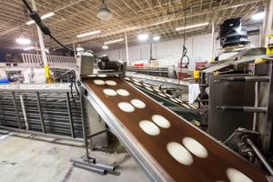 Tortilla dough travels along conveyer belts to the ovens at Tortillas Incorporated, a family-owned tortilla factory, in North Las Vegas January 22, 2015.