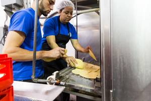 Danelia Gonzalez, right, and a co-worker load freshly made tortillas into the tostada oven while working at Tortillas Incorporated, a family-owned tortilla factory, in North Las Vegas January 22, 2015.
